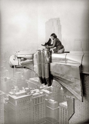 American photographer and journalist Margaret Bourke-White (1904 - 1971) perches on an eagle head gargoyle at the top of the Chrysler Building and focuses a camera, New York, New York, 1935. (Photo by Oscar Graubner/Time Life Pictures/Getty Images)
